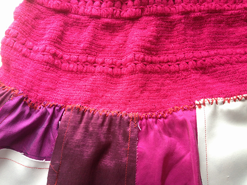 Hand zig-zag stitching skirt patchwork to woolly top.png
